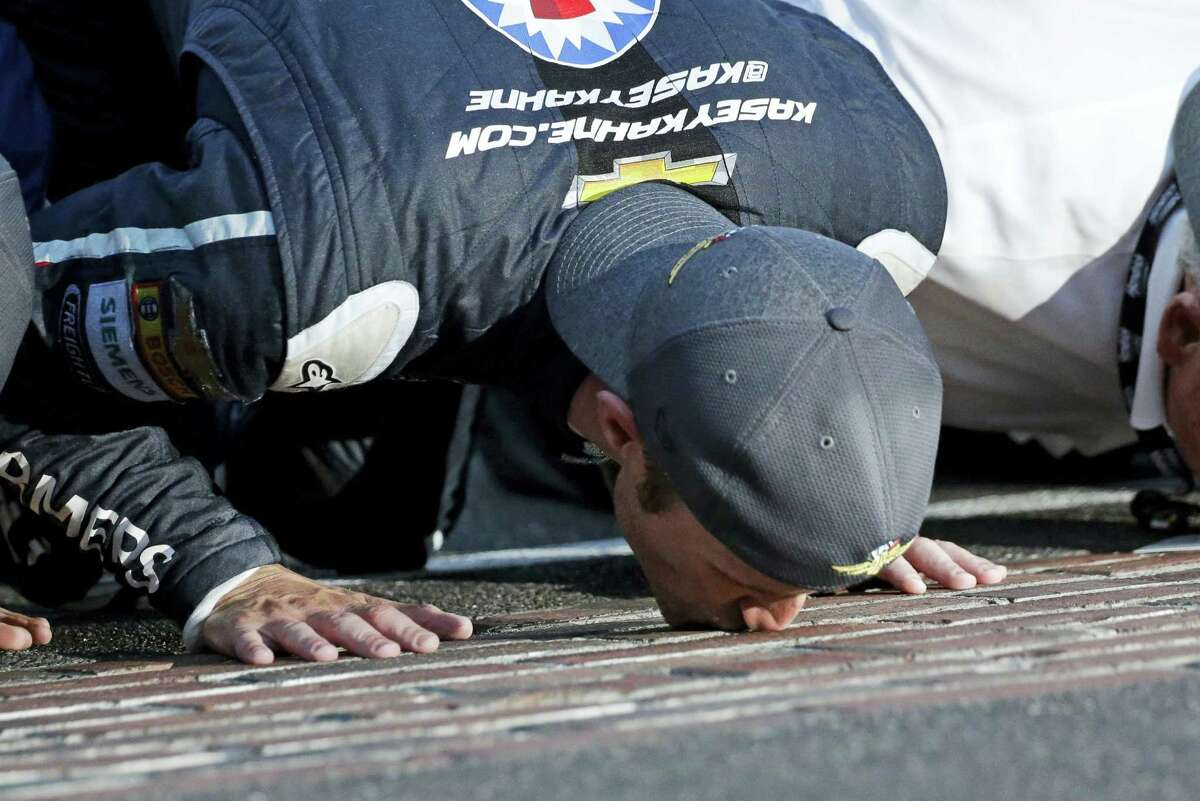 Kasey Kahne (5) kisses the bricks on the start/finish line after winning the Brickyard 400 at Indianapolis Motor Speedway on Sunday.