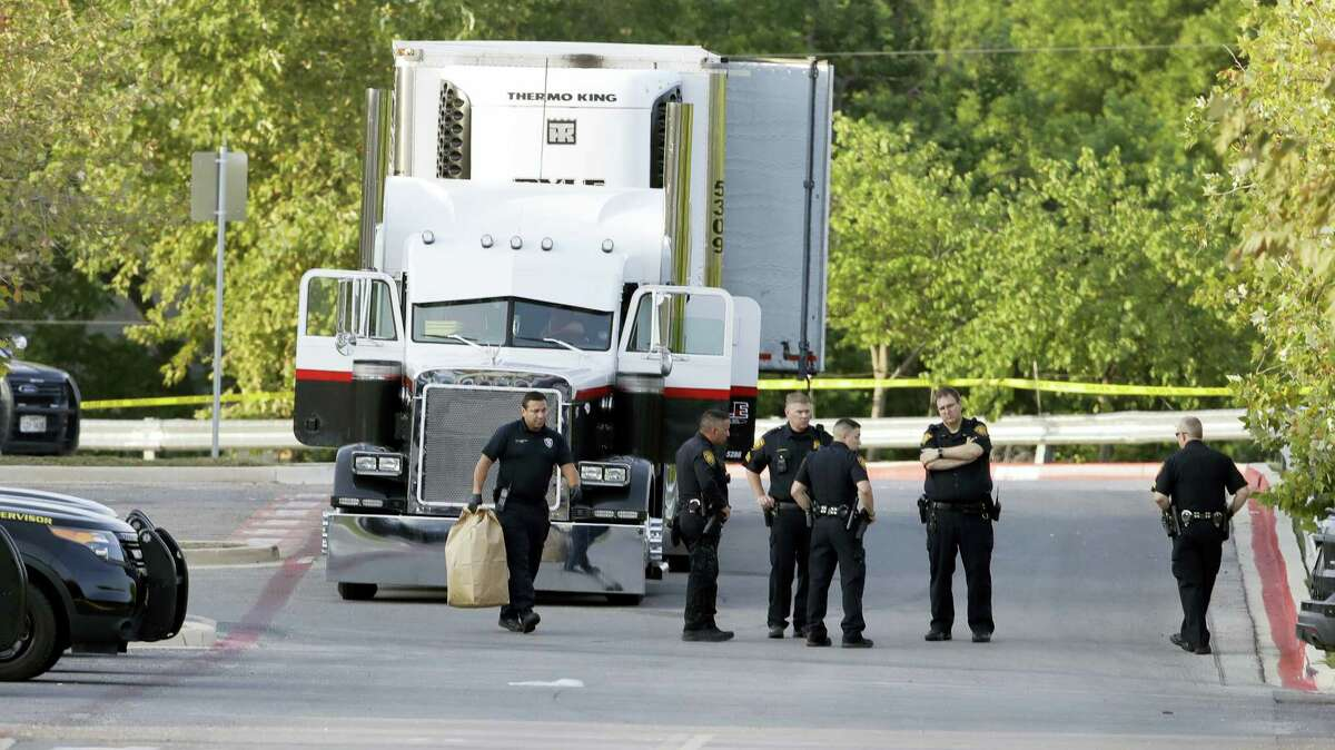 San Antonio police officers investigate the scene on July 23, 2017 where eight people were found dead in a tractor-trailer loaded with at least 30 others outside a Walmart store in stifling summer heat in what police are calling a horrific human trafficking case, in San Antonio.