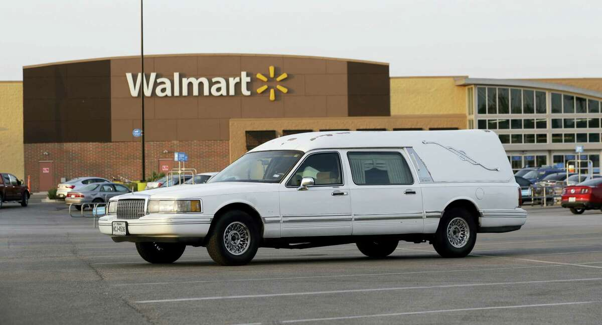 A hearse sits in the parking lot of a Walmart store where eight people were found dead in a tractor-trailer loaded with at least 30 others outside in stifling summer heat in what police are calling a horrific human trafficking case on July 23, 2017, in San Antonio.