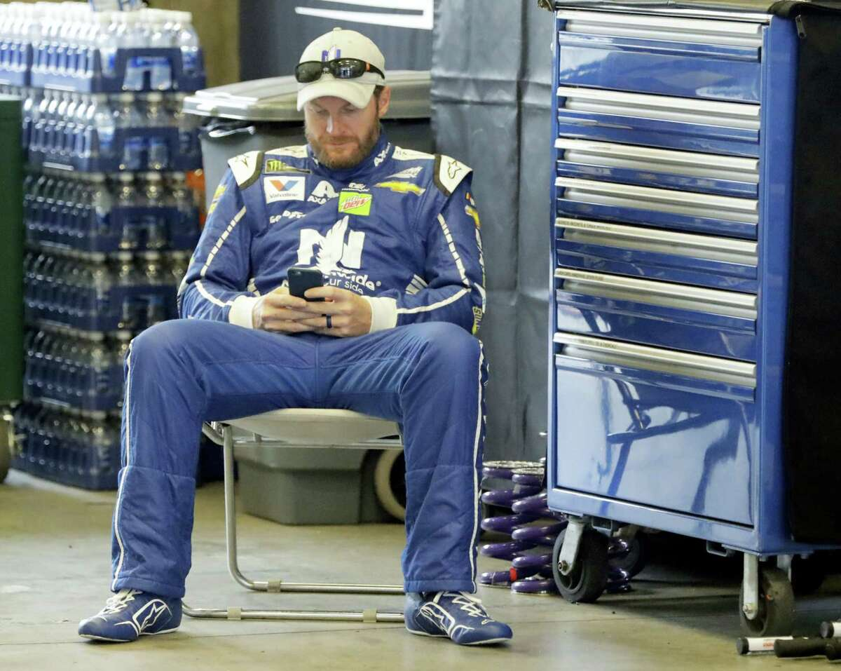 Dale Earnhardt Jr. looks at his phone before a practice session at Indianapolis Motor Speedway.