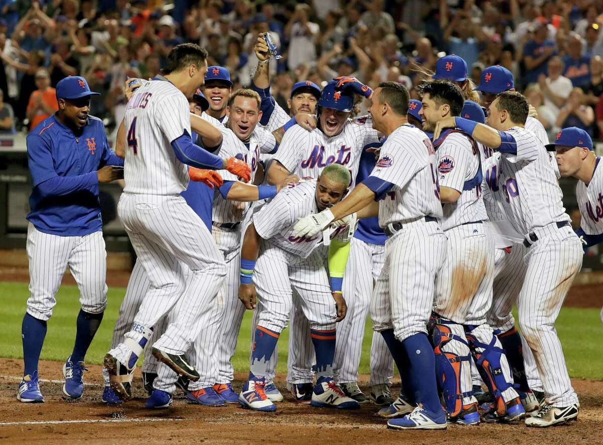 The Mets' Wilmer Flores, bottom center, is greeted by teammates at home plate after hitting a walk-off home run against the A's on Saturday.