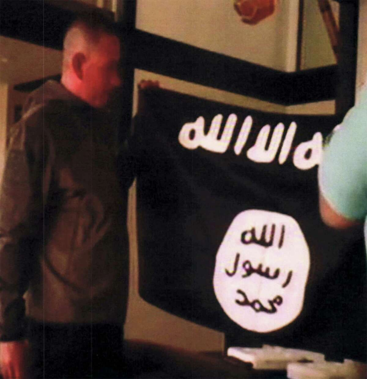 In this July 8, 2017, file image taken from FBI video and provided by the U.S. Attorney's Office in Hawaii on July 13, 2017, Army Sgt. 1st Class Ikaika Kang holds an Islamic State group flag after allegedly pledging allegiance to the terror group at a house in Honolulu. A federal grand jury in Hawaii has indicted Kang for attempting to provide material support to the Islamic State group. Kang was indicted Friday, July 21 after he was arrested by an FBI SWAT team on July 8. Kang was ordered held without bail. Because of the indictment, Kang will no longer have a preliminary hearing that was scheduled for Monday, July 24.