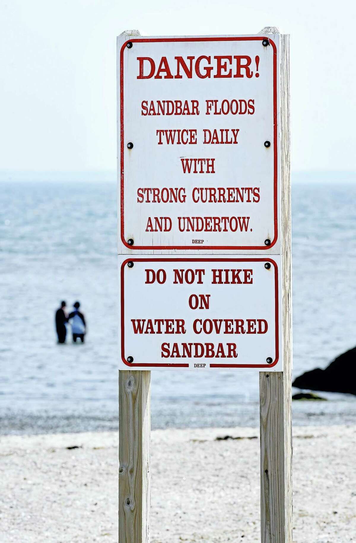 Signs posted at Silver Sands State Park in Milford warn of the danger of crossing the sandbar to Charles Island.
