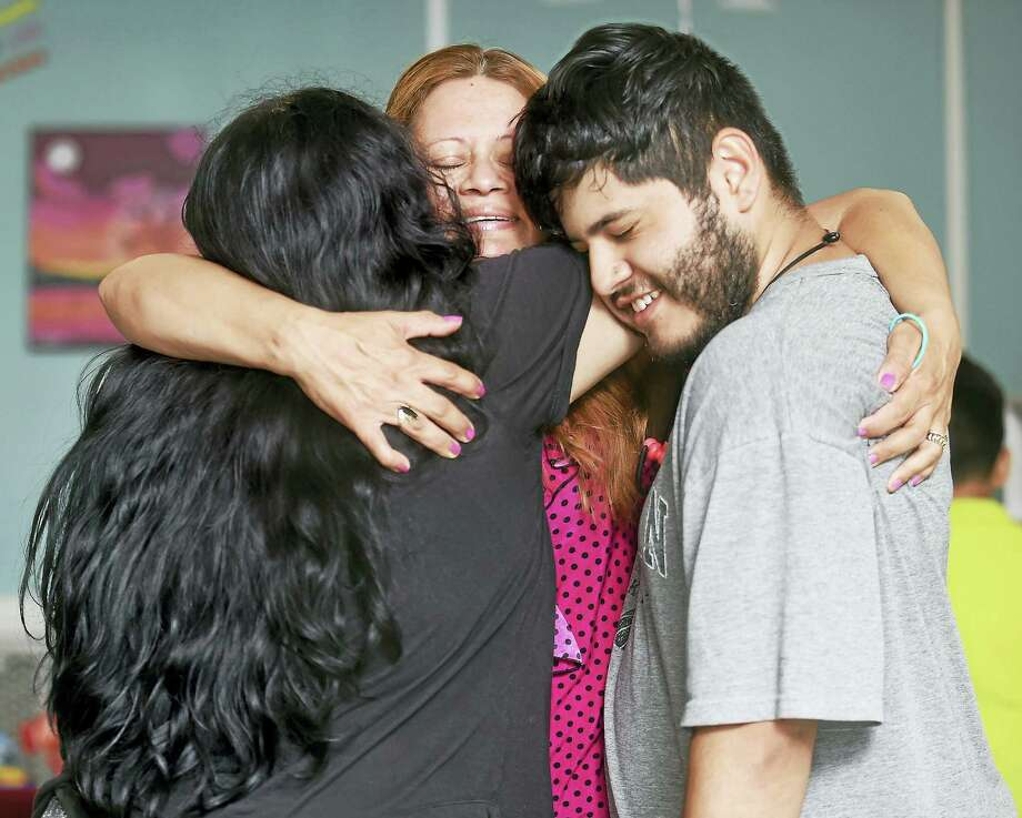 Nury Chavarria (center) of Norwalk hugs her daughter, Lindsay Chavarria (left) and son, Elvin Martinez, in a room where she is staying  with another daughter, Hayley, 9, at Iglesia de Dios Pentecostal in the Fair Haven section of New Haven during a visit on 7/22/2017.  Arnold Gold / Hearst Connecticut Media Photo: Digital First Media
