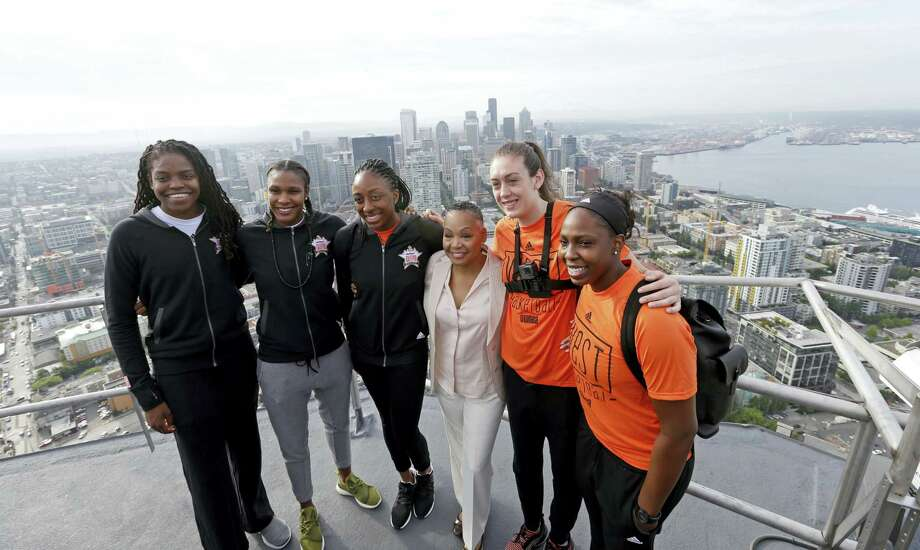WNBA basketball All-Star players Connecticut Sun's Jonquel Jones, left, Minnesota Lynx's Rebekkah Brunson, Los Angeles Sparks' Nneka Ogwumike, WNBA president Lisa Borders, Seattle Storm's Breanna Stewart and Sparks' Chelsea Gray stand on a platform in view of downtown Seattle and Elliott Bay about 575-feet high atop the Space Needle after raising the league flag atop the structure Friday. The WNBA All-Star game is Saturday in Seattle. Photo: Elaine Thompson — The Associated Press  / Copyright 2017 The Associated Press. All rights reserved.