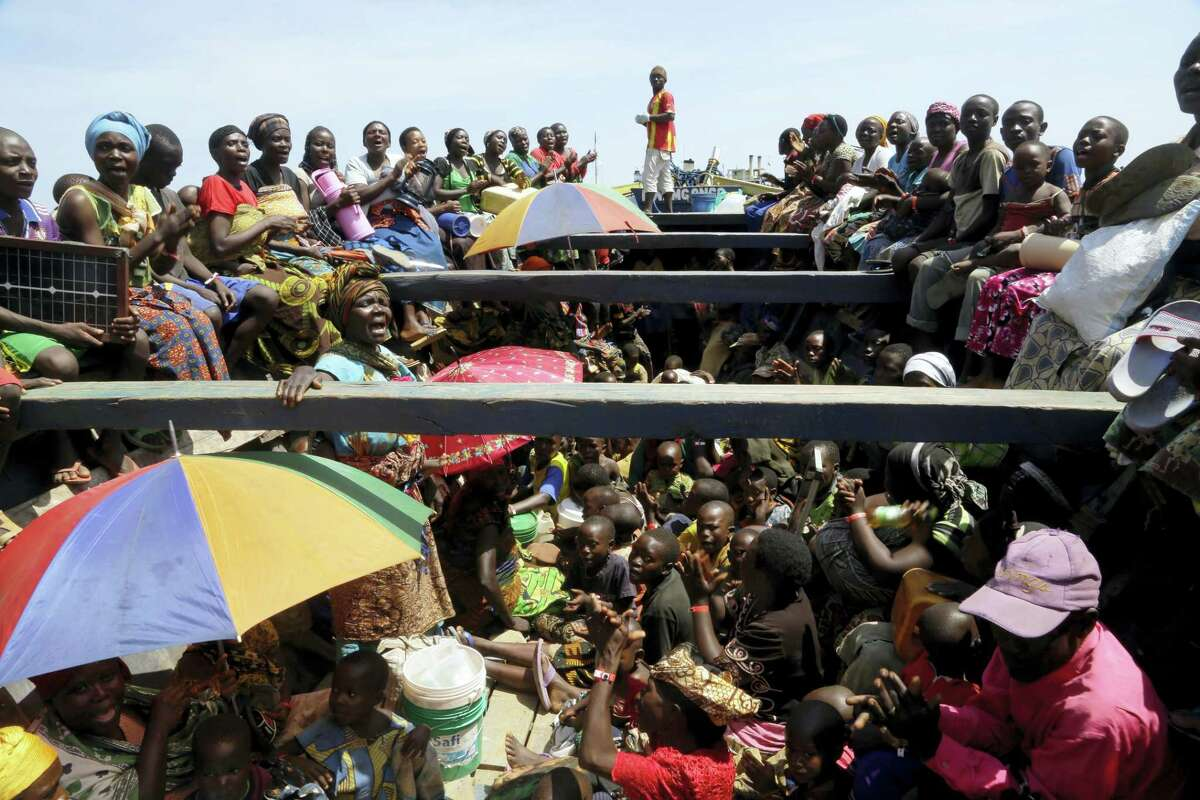 In this Saturday, May 23, 2015, file photo, refugees who fled Burundi's violence and political tension sing in a speedboat taking them to a ship freighted by the UN, at Kagunga on Lake Tanganyika, Tanzania.