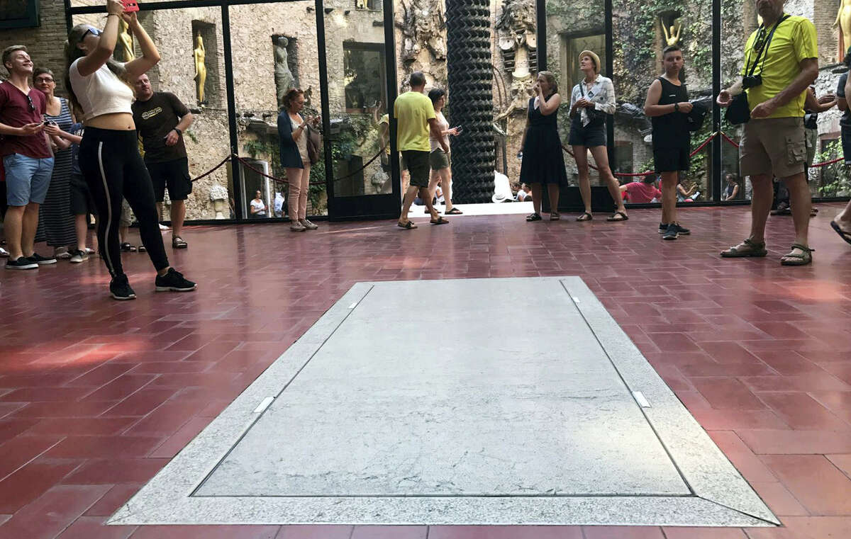 Visitors stand near the tomb of Salvador Dali inside Dali Museum Theatre in Figueres, Spain, Friday, July 21, 2017. The samples of hair, nails and two long bones removed overnight from Salvador Dali's embalmed remains could open a judicial battle for the artist's estate if genetic tests prove that he had fathered a girl decades ago. Forensic experts removed on Thursday night the biological samples from a crypt in Figueres, in a sensitive operation that involved pulleys lifting a 1.5-ton stone slab.