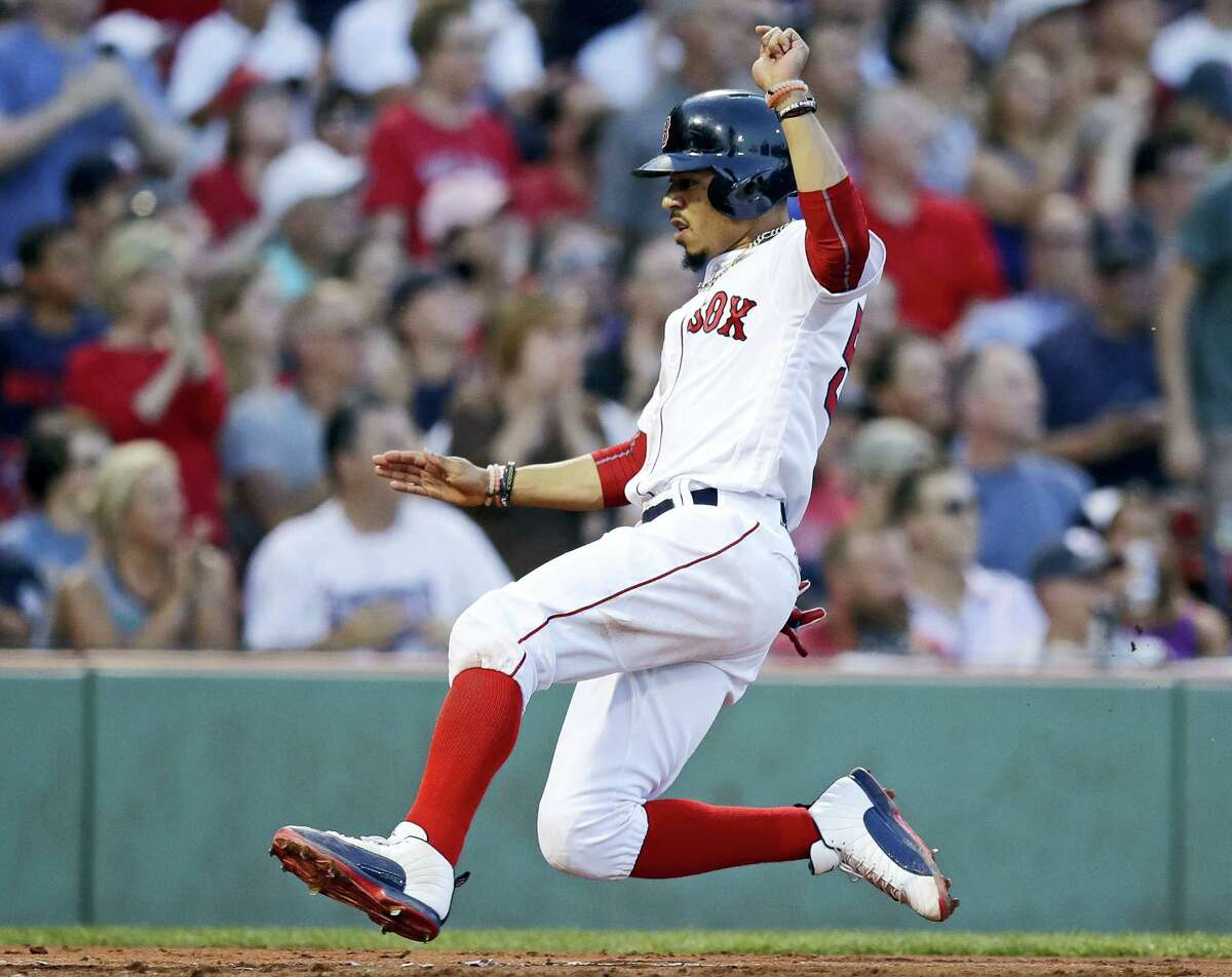 Boston Red Sox's Mookie Betts scores on a two RBI single by Dustin Pedroia during the second inning of a baseball game against the Toronto Blue Jays at Fenway Park in Boston, on Wednesday.