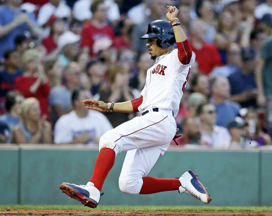 Boston Red Sox's Mookie Betts scores on a two RBI single by Dustin Pedroia during the second inning of a baseball game against the Toronto Blue Jays at Fenway Park in Boston, on Wednesday. Photo: Charles Krupa - The Associated Press  / Copyright 2017 The Associated Press. All rights reserved.