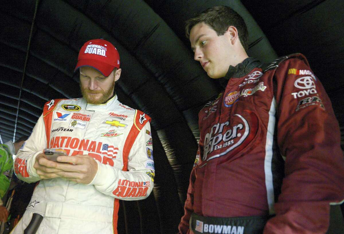 In this file photo, Alex Bowman, right, watches as Dale Earnhardt Jr. sends out a tweet while waiting under a tunnel for driver introductions to begin before a NASCAR Sprint Cup Series auto race at the Daytona International Speedway, in Daytona Beach, Fla. Dale Earnhardt Jr. got the replacement he wanted. Alex Bowman got his dream job. Hendrick Motorsports announced Thursday that the 24-year-old Bowman will replace one of the series' biggest stars in the No. 88 car next season after Earnhardt retires.