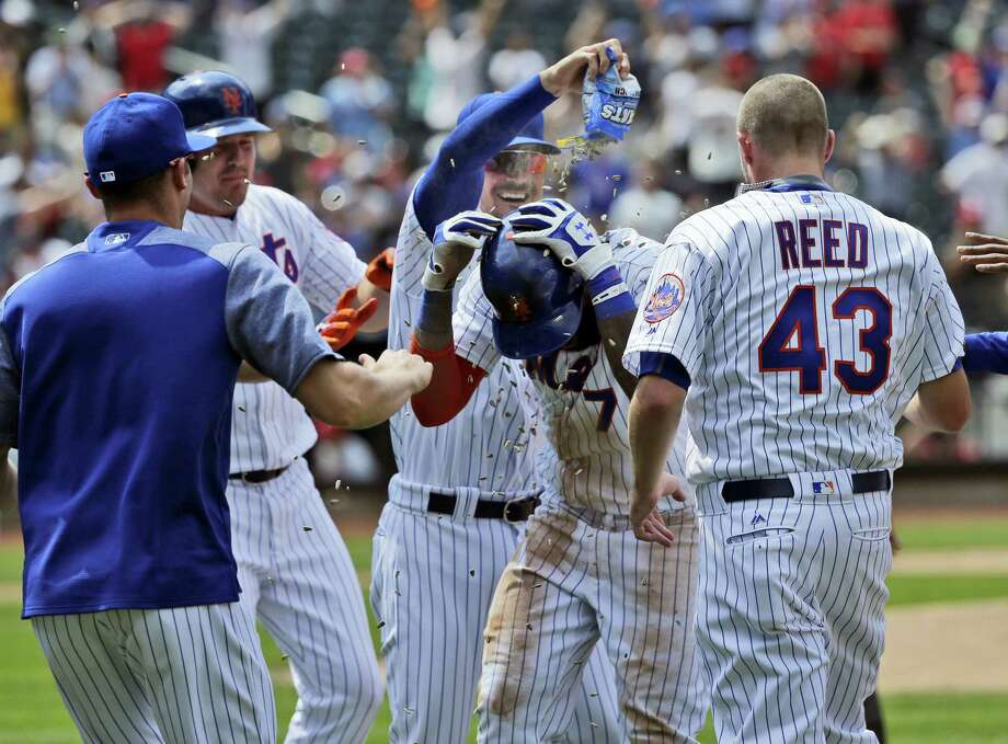 The Mets' Jose Reyes, center, is mobbed by teammates after hitting a walk-off RBI single against the Cardinals at Citi Field on Thursday. Photo: Seth Wenig — The Associated Press  / Copyright 2017 The Associated Press. All rights reserved.