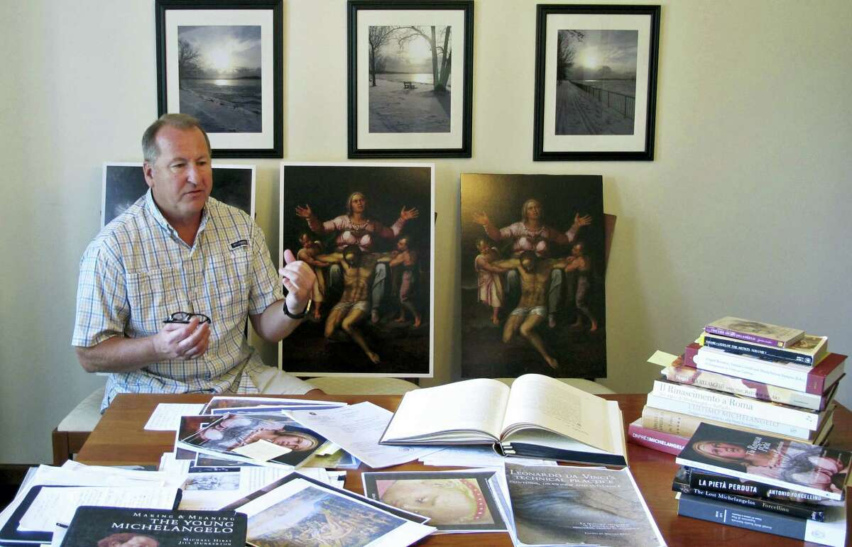 In this June 26, 2017, photo, Martin Kober displays at his home in Tonawanda, N.Y. literature and copies of a family heirloom that he believes was painted by Renaissance master Michelangelo. Kober is convinced the painting of a dying Jesus that hung above the mantel in his upstate New York childhood home is the work of Michelangelo. Getting experts to agree remains the $300 million hurdle.