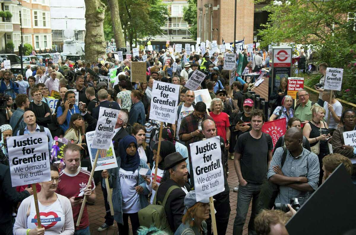 People protest ahead of a meeting of Kensington and Chelsea Council at Kensington Town Hall in west London, Wednesday July 19, 2017, the local authority in control of response to the recent Grenfell Tower fire. The fire at the Grenfell Tower residential bloc left dozens dead.