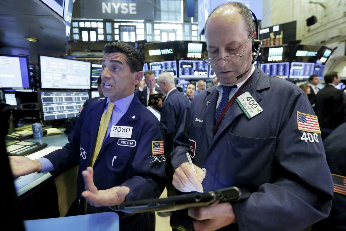 Specialist Peter Mazza, left, and trader Gordon Charlop work on the floor of the New York Stock Exchange Thursday.