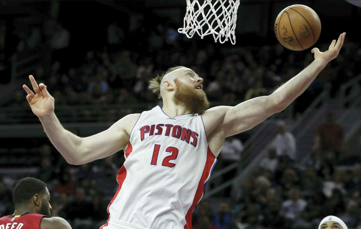 FILE- In this file photo, Detroit Pistons center Aron Baynes reaches for a rebound during the second half of an NBA basketball game against the Miami Heat in Auburn Hills, Mich. The Boston Celtics have signed Baynes, a free agent, on Wednesday. The 6-foot-10 former Pistons and Spurs center has averaged 5.2 points and 4.1 rebounds in his career.