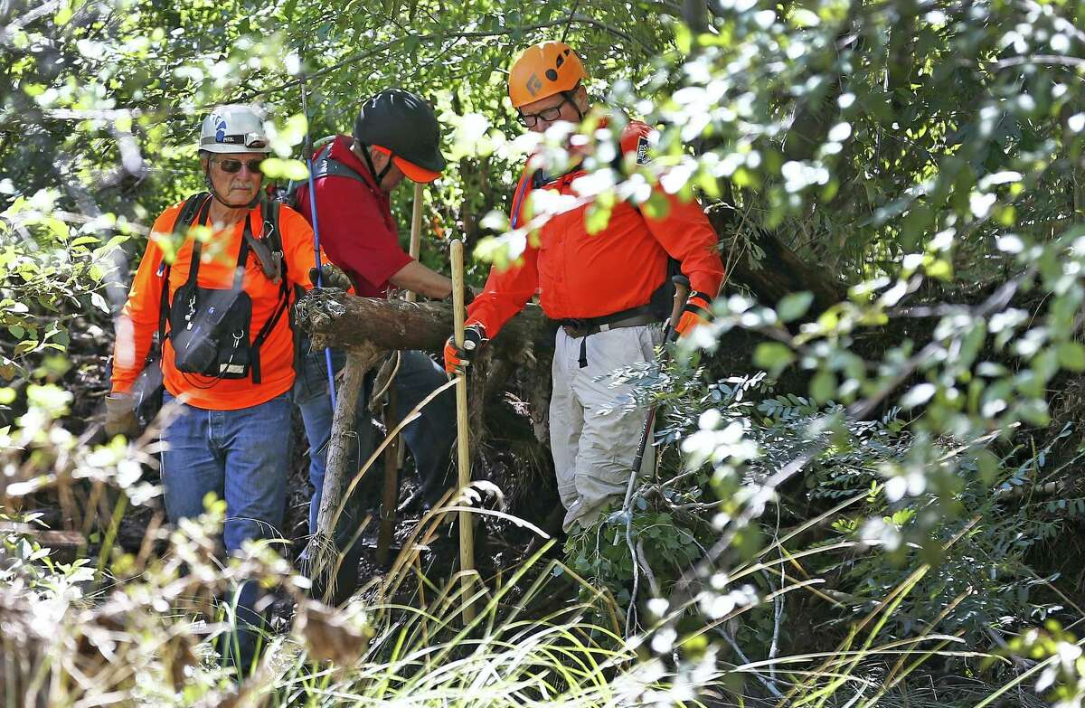 Members of the Tonto Rim Search and Rescue Team comb the muddy East Verde River near the entrance to the First Crossing recreation area during the search and rescue operation for a victim in a flash flood Monday, July 17, 2017, in Payson, Ariz. The bodies of several children and adults have been found after Saturday's flash flooding poured over a popular swimming area in the Tonto National Forest.