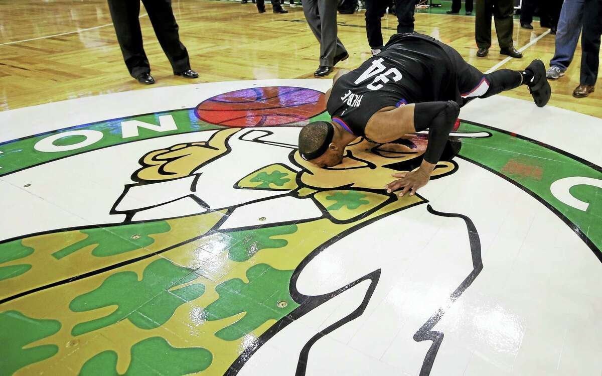 Paul Pierce, as a member of the Clippers, bends down to kiss the Boston Celtics logo following his final game in Boston.