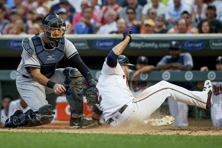 Yankees catcher Austin Romine tags out the Twins' Brian Dozier during the third inning on Monday. Photo: Bruce Kluckhohn — The Associated Press  / FR170893 AP