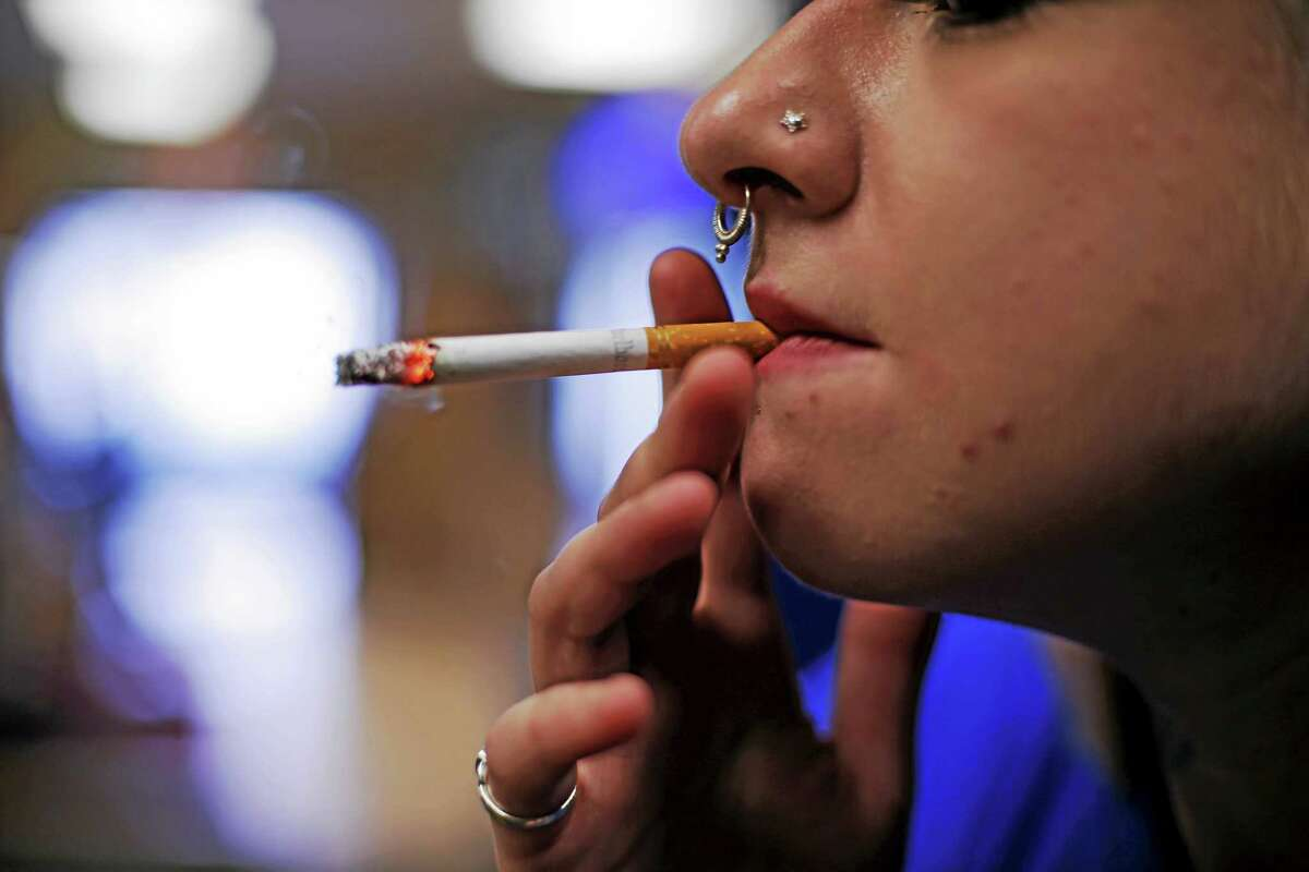 In this file photo, store manager Stephanie Hunt smokes a Marlboro cigarette while posing for photos at a Smoker Friendly shop in Pittsburgh.