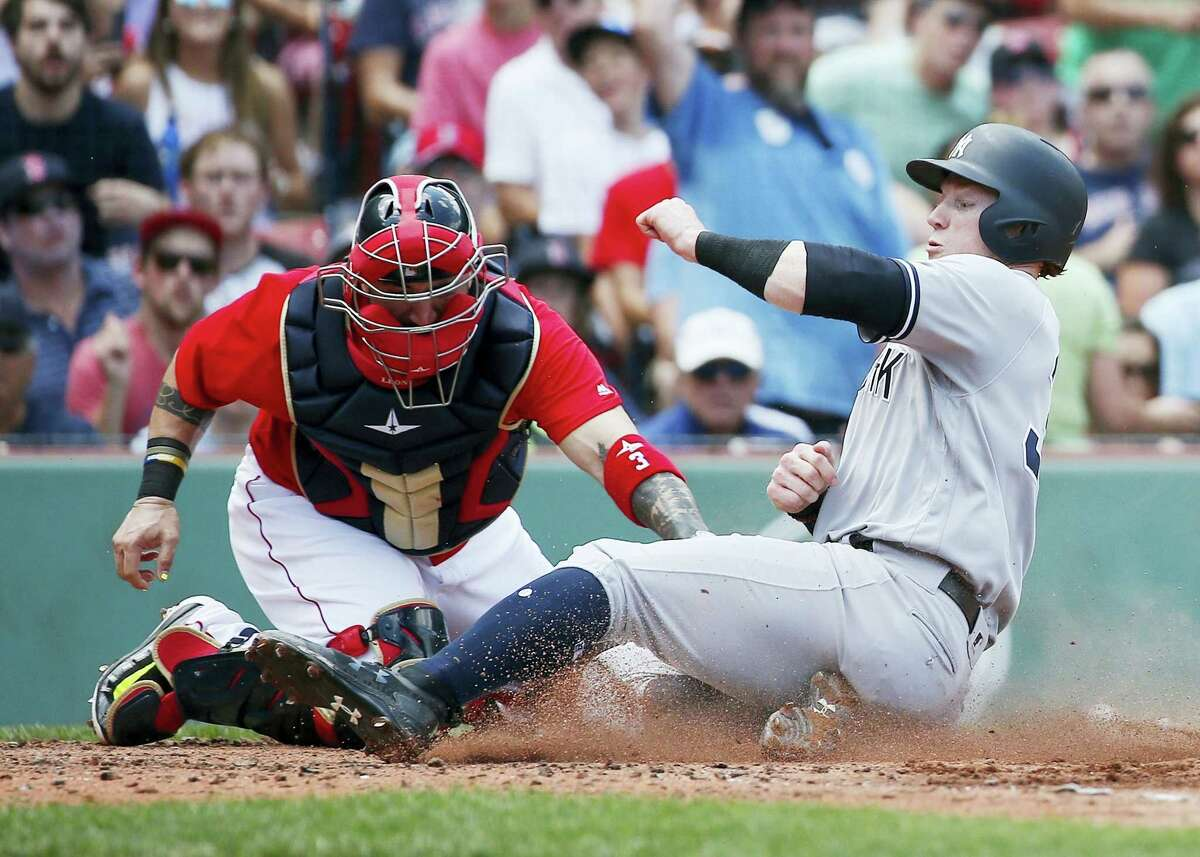 The Yankees' Clint Frazier, right, scores during the fourth inning of the first game of a doubleheader in Boston on Sunday.