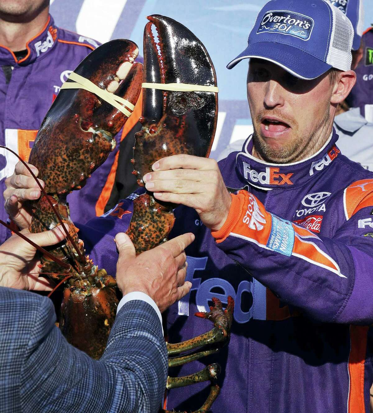 Driver Denny Hamlin reacts as he is handed a lobster after winning at the New Hampshire Motor Speedway in Loudon, N.H., on Sunday.