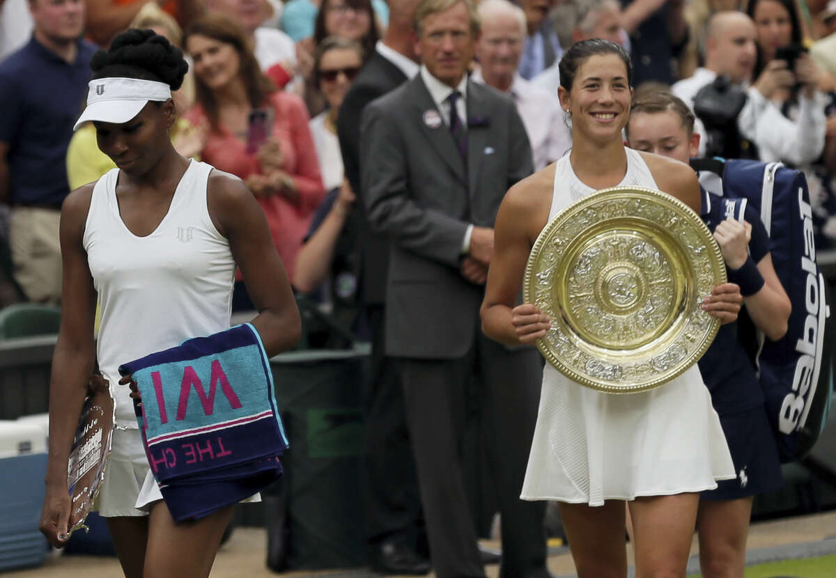 Venus Williams, left, leaves with her runner-up trophy after losing to Spain's Garbine Muguruza in the women's singles final at Wimbledon on Saturday.