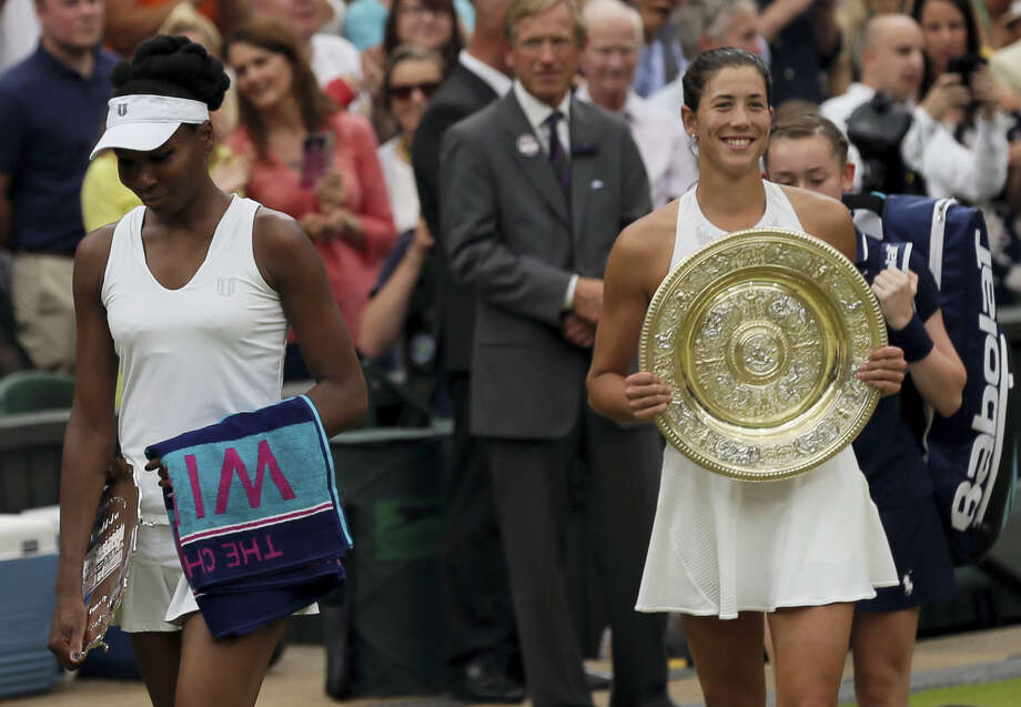 Venus Williams, left, leaves with her runner-up trophy after losing to Spain's Garbine Muguruza in the women's singles final at Wimbledon on Saturday. Photo: Tim Ireland — The Associated Press  / Copyright 2017 The Associated Press. All rights reserved.