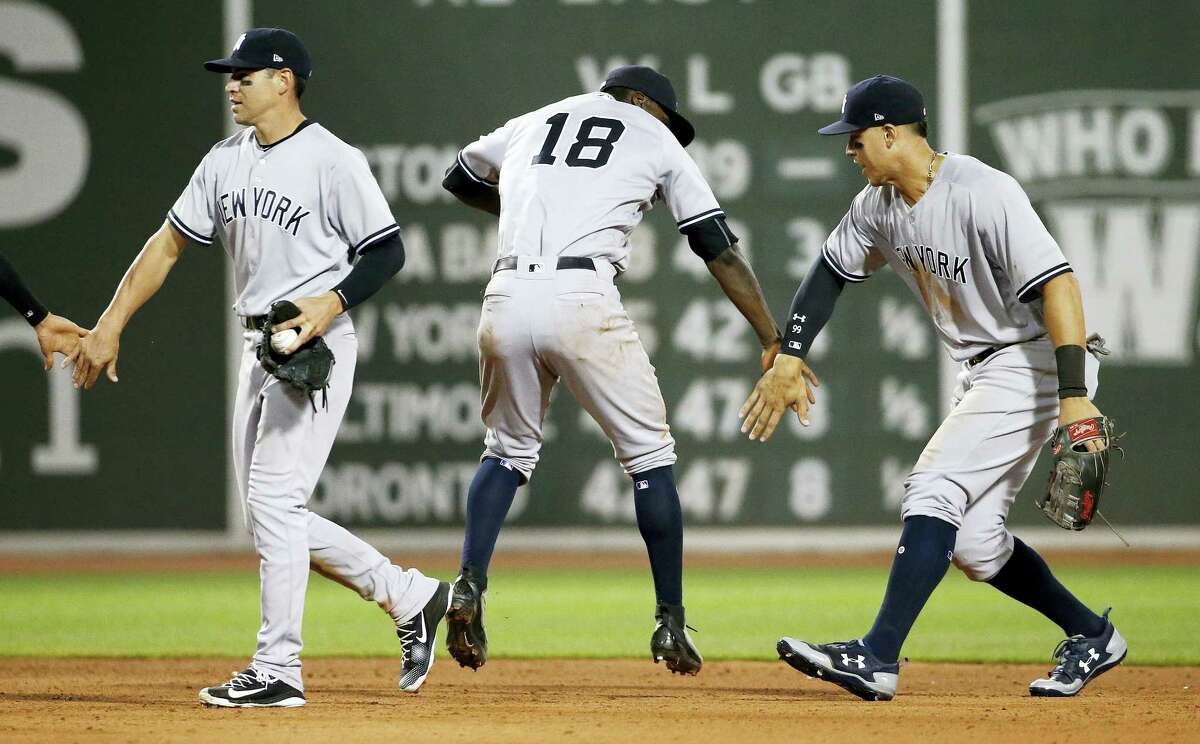 From left, the Yankees' Jacoby Ellsbury, Didi Gregorius and Aaron Judge celebrate after the Yankees beat the Red Sox 4-1 in 16 innings on Saturday.