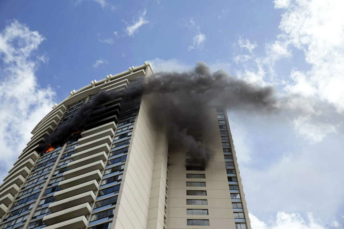 Smoke billows from the upper floors of the Marco Polo apartment complex, Friday, July 14, 2017, in Honolulu.