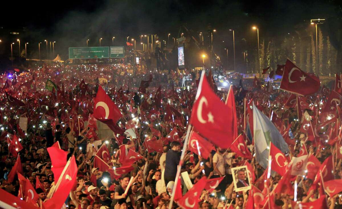 """Crowd cheer as Turkey's President Recep Tayyip Erdogan speaks at the July 15 Martyr's bridge on a """"National Unity March"""" to commemorate the one year anniversary of the July 15, 2016, botched coup attempt, in Istanbul, Saturday, July 15, 2017. Turkey commemorates the first anniversary of the July 15 failed military attempt to overthrow president Erdogan, with a series of events honoring some 250 people, who were killed across Turkey while trying to oppose coup-plotters."""