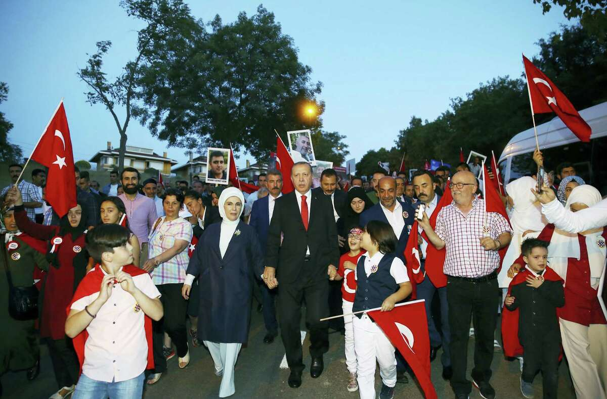 Turkey's President Recep Tayyip Erdogan, centre, accompanied by his wife Emine, left, march with relatives of victims of the July 15, 2016, failed coup attempt, as he arrives close to the July 15 Martyr's bridge to commemorate the one year anniversary of the coup attempt, in Istanbul, Saturday, July 15, 2017. Turkey commemorates the first anniversary of the July 15 failed military attempt to overthrow Erdogan, with a series of events honoring some 250 people, who were killed across Turkey while trying to oppose coup-plotters.