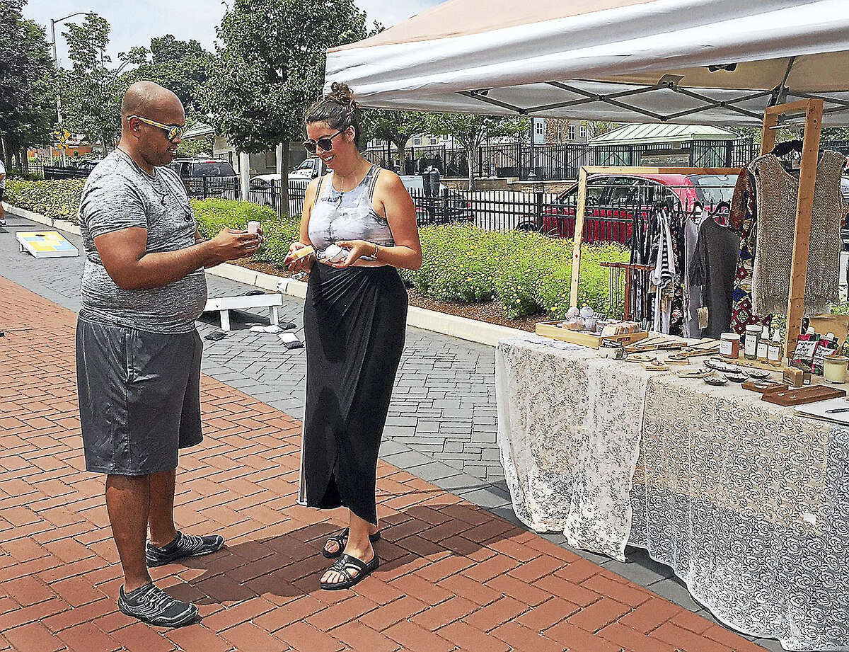 Meagan Cann of Workspace Collective shows handmade soaps to Joseph Purayidthil during the Downtown Chow-Down in Danbury Thursday.