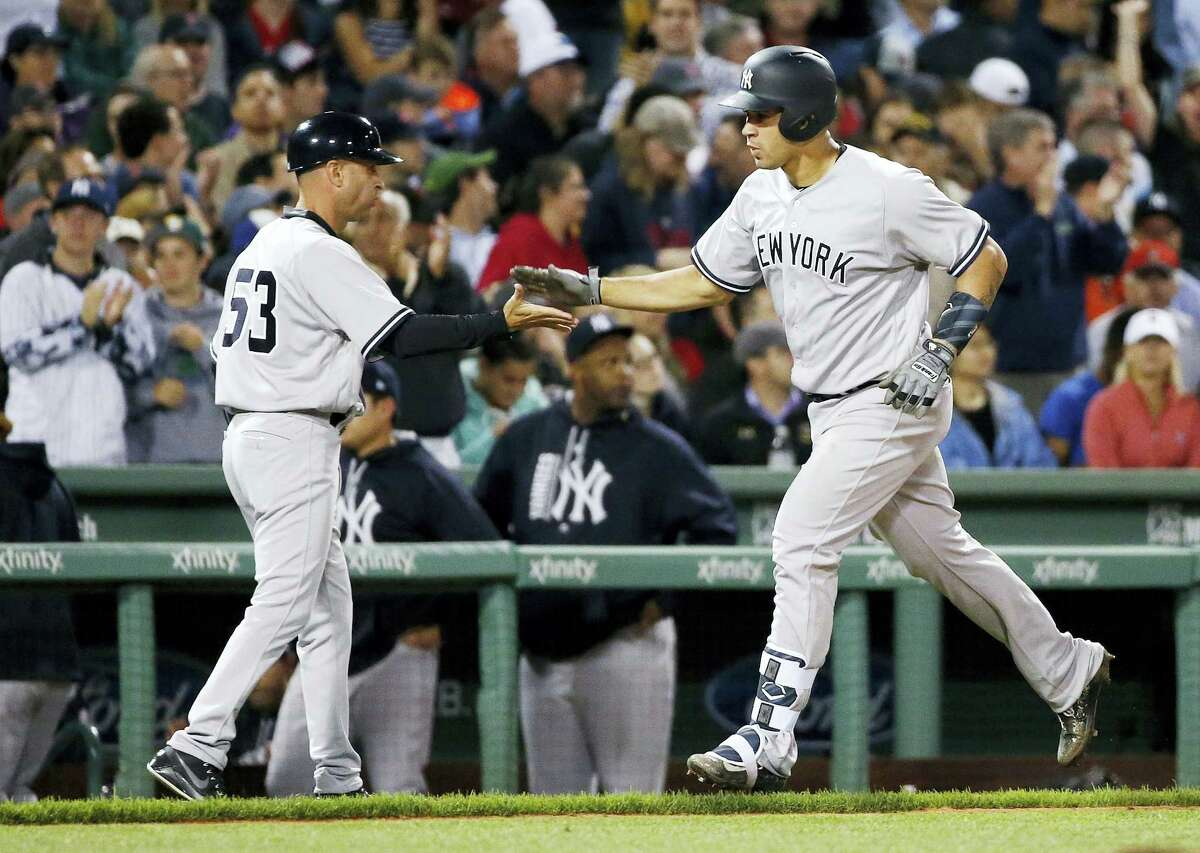 New York Yankees' Gary Sanchez celebrates his two-run home run with third base coach Joe Espada (53) during the fifth inning of a baseball game in Boston, Friday.
