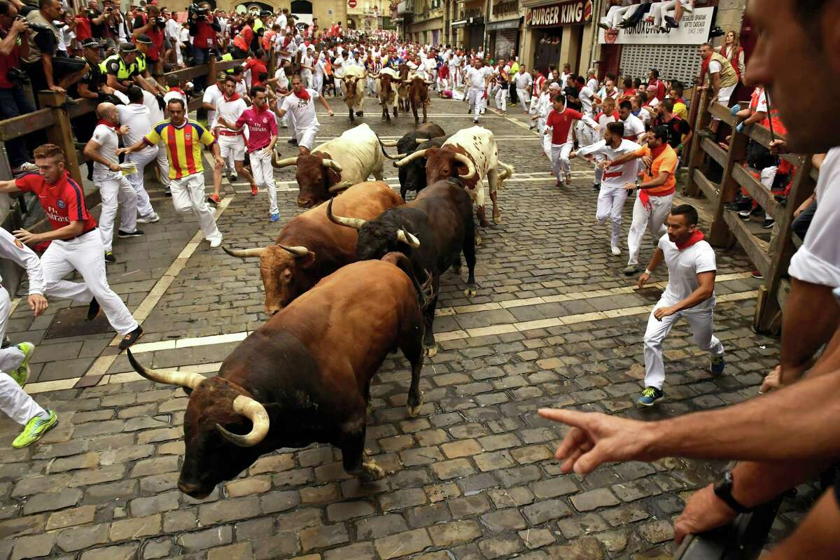 Revellers run next to Nunez del Cuvillo's fighting bulls during the running of the bulls at the San Fermin Festival in Pamplona, northern Spain, Thursday, July 13, 2017. Revellers from around the world flock to Pamplona every year to take part in the eight days of the running of the bulls.