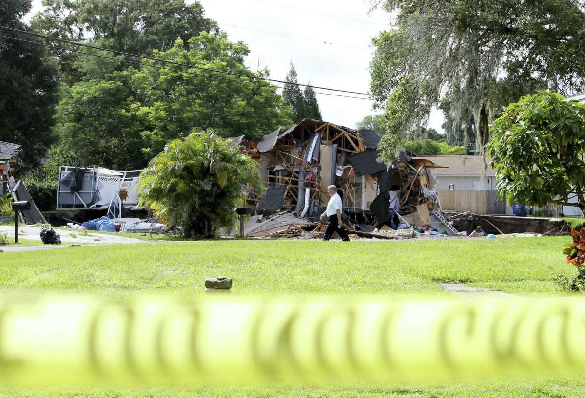 Debris is strewn about from a partially collapsed home in Land O' Lakes, Fla. on Friday, July 14, 2017.A sinkhole that started out the size of a small swimming pool and continued to grow has swallowed a home in Florida and severely damaged another.