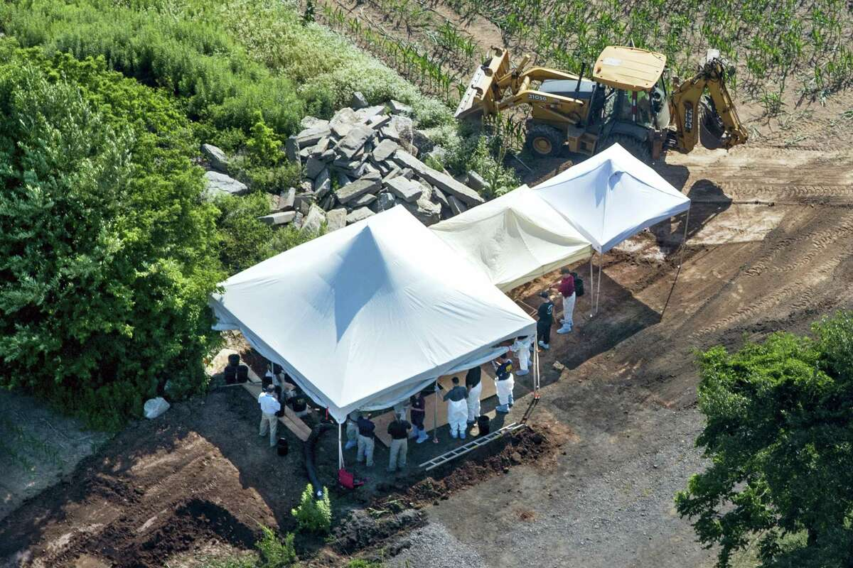 Investigators gather under tents as they search a property on July 12, 2017 in Solebury, Pa., for four missing young Pennsylvania men feared to be the victims of foul play.