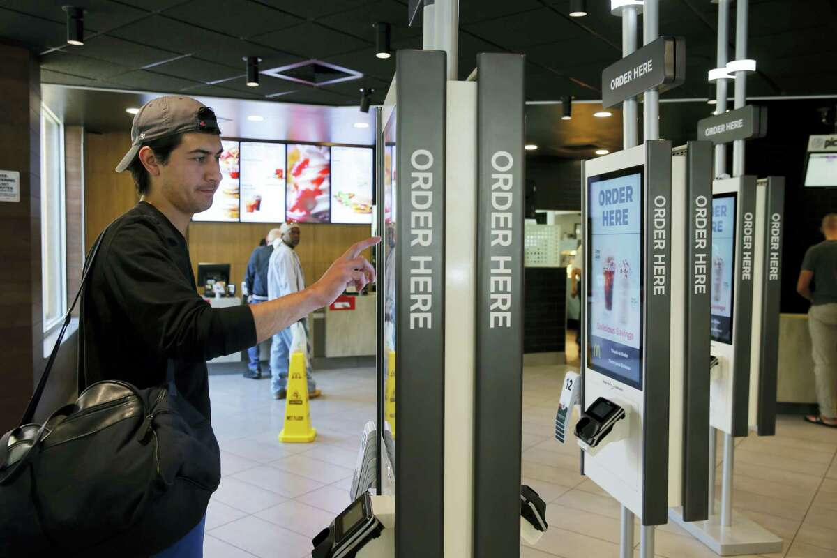 In this Thursday photo, Brandon Alba from Milwaukee, orders food at a self-service kiosk at a McDonald's restaurant in Chicago. The company that helped define fast food is making supersized efforts to reverse its fading popularity and catch up to a landscape that has evolved around it. That includes expanding delivery, digital ordering kiosks in restaurants, and rolling out an app that saves precious seconds.