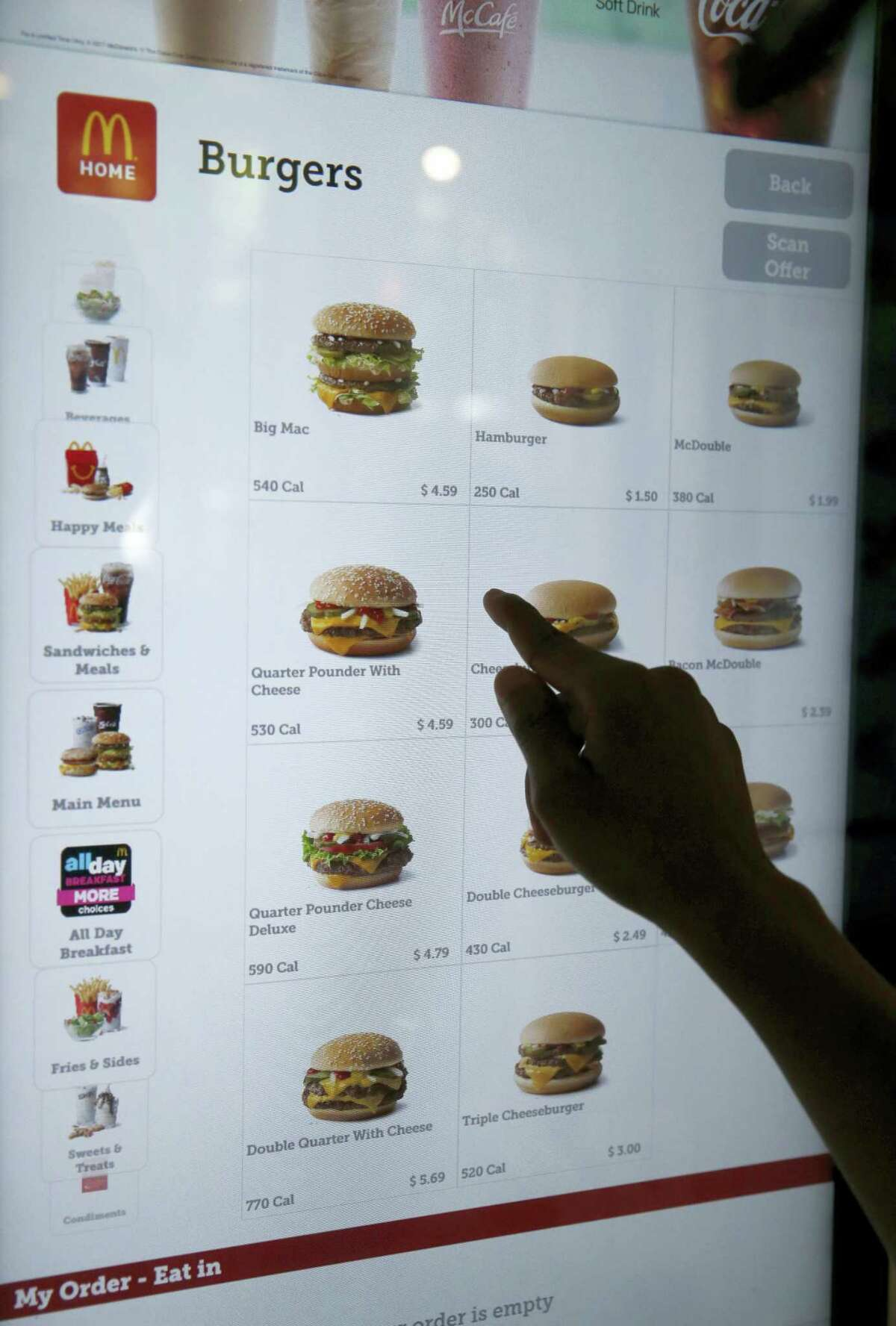 In this Thursday photo, a customer orders food at a self-service kiosk at a McDonald's restaurant in Chicago. The company that helped define fast food is making supersized efforts to reverse its fading popularity and catch up to a landscape that has evolved around it. That includes expanding delivery, digital ordering kiosks in restaurants, and rolling out an app that saves precious seconds.