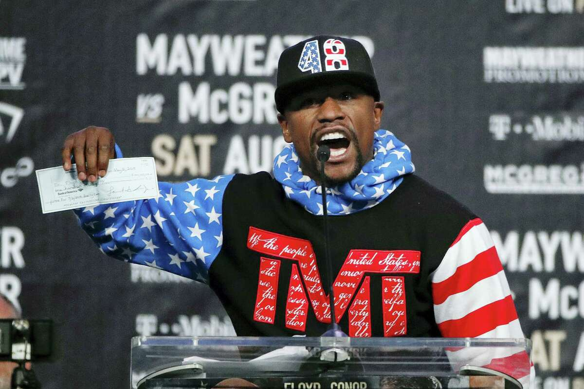 Floyd Mayweather Jr. holds up a check while speaking at a news conference at Staples Center Tuesday in Los Angeles.