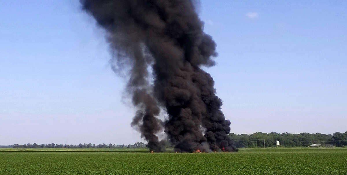 In this photo provided by Jimmy Taylor, smoke and flames rise into the air after a military transport airplane crashed in a field near Itta Bena, Miss., on the western edge of Leflore County July 10, 2017, killing several. (Jimmy Taylor via AP)