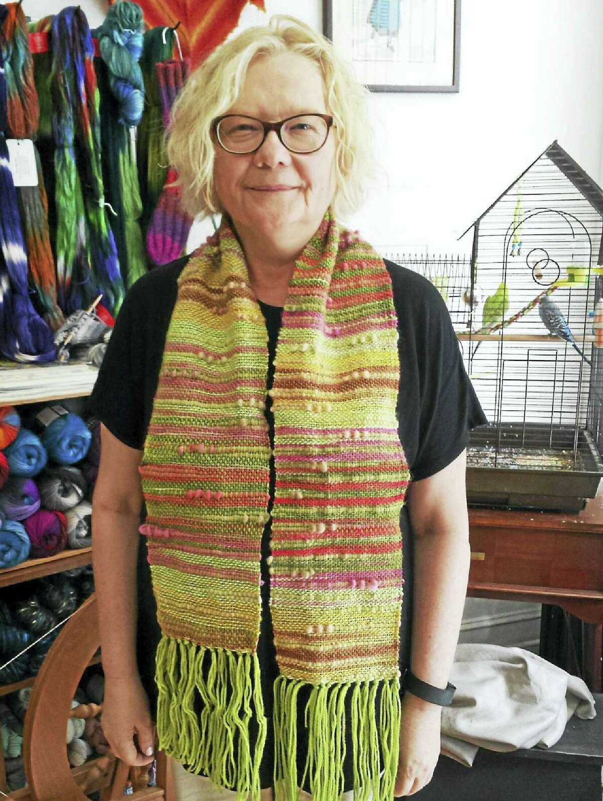 A student proudly shows her first woven scarf, hot off the loom.