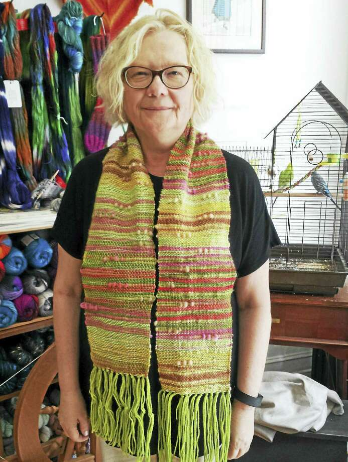 A student proudly shows her first woven scarf, hot off the loom. Photo: Photo By Ginger Balch