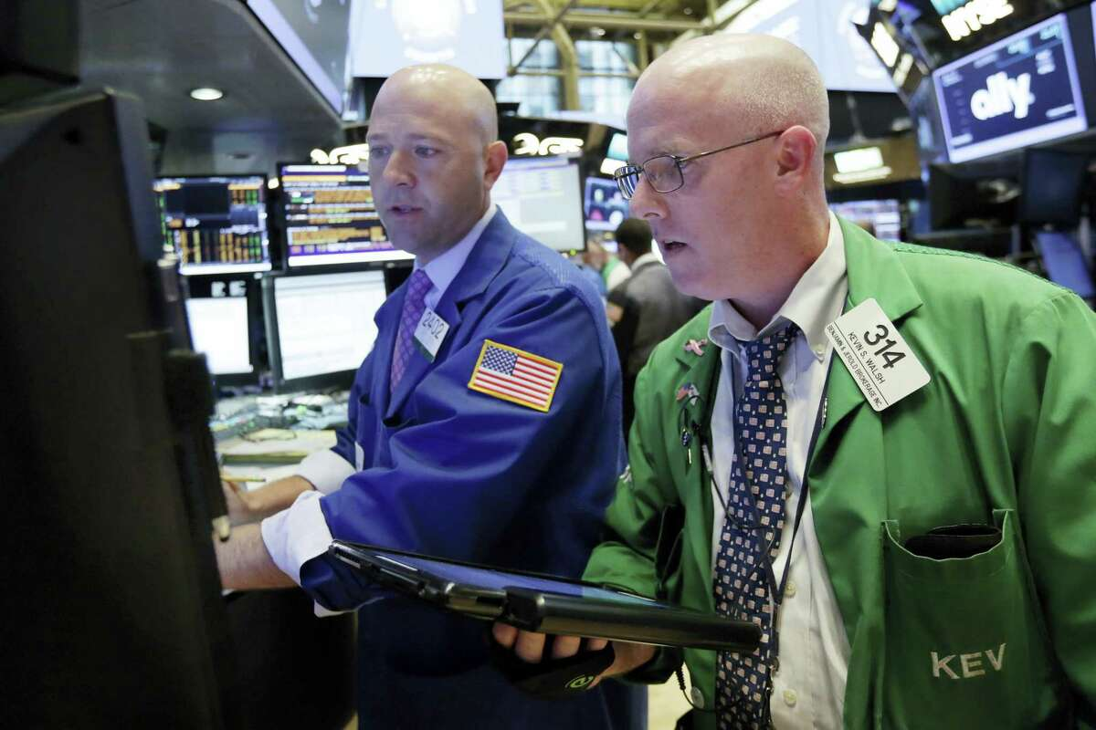 Specialist Jay Woods, left, and trader Kevin Walsh work on the floor of the New York Stock Exchange Wednesday.