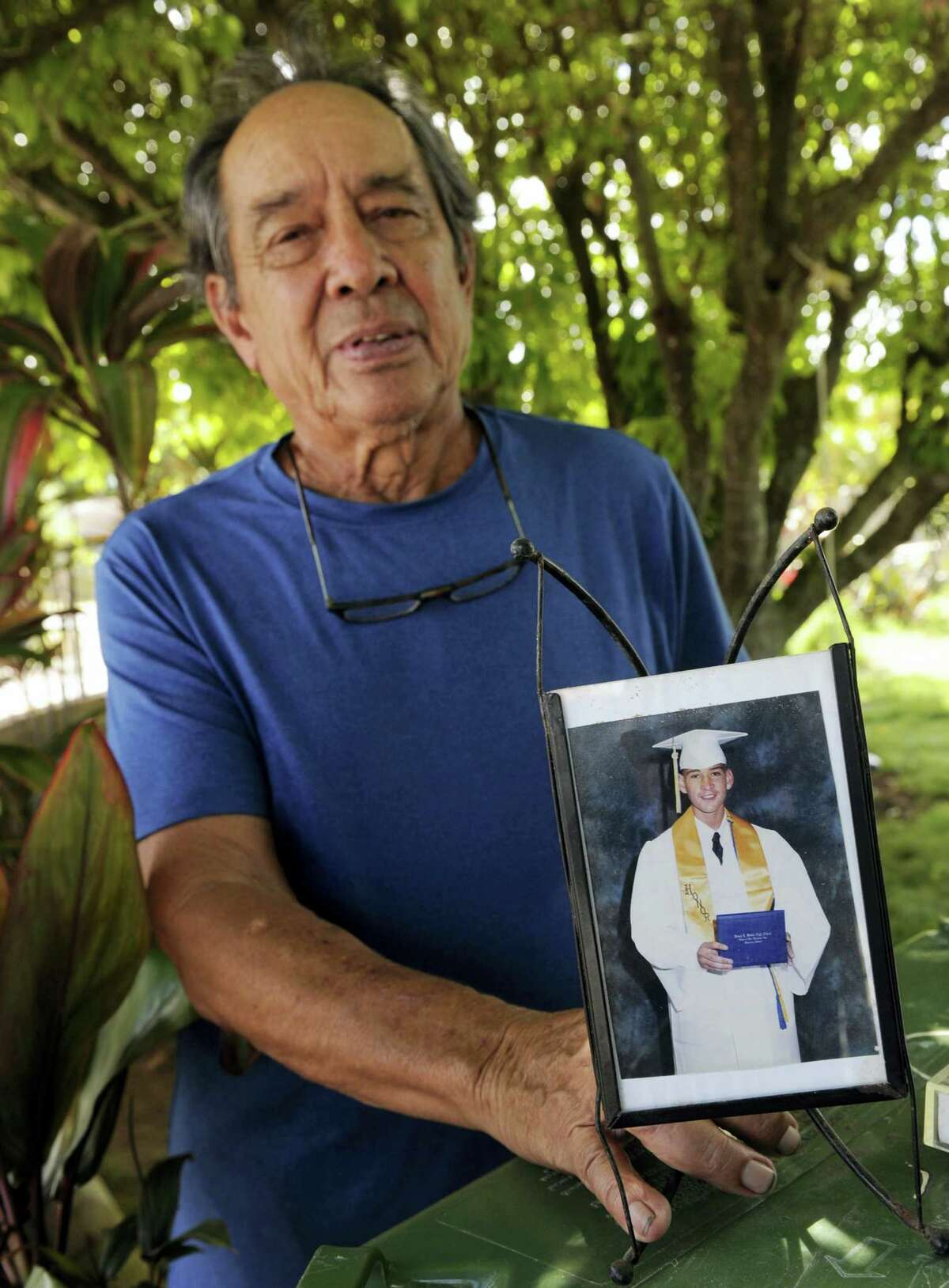 """In this Monday, July 10, 2017 photo, Clifford Kang, father of soldier Ikaika E. Kang, poses with photo of his son in Kailua, Hawaii. Ikaika E. Kang, an active-duty U.S. soldier, was arrested over the weekend on terrorism charges that accuse him of pledging allegiance to the Islamic State group and saying he wanted to """"kill a bunch of people."""""""