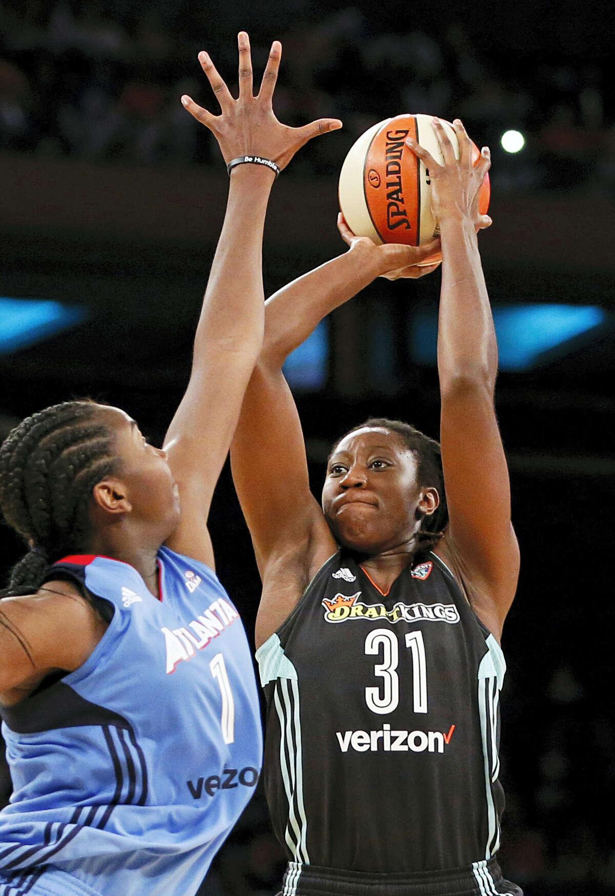 New York Liberty center Tina Charles shoots with Atlanta Dream center Elizabeth Williams defending.