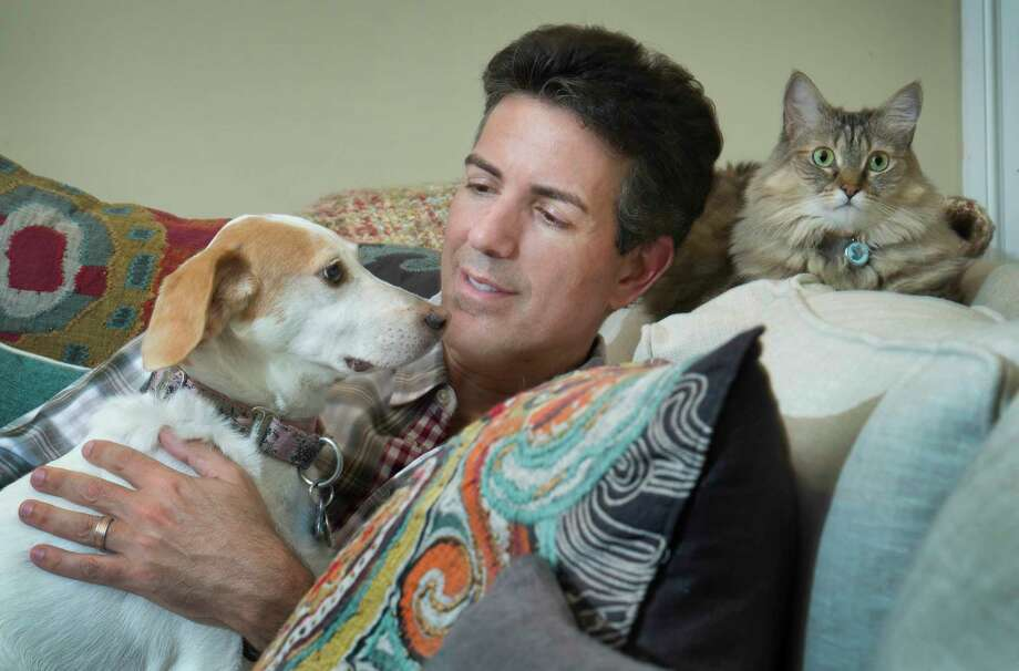Humane Society executive Wayne Pacell at home with his dog Lily and cat, Zoe; research has shown that when humans interact with dogs, oxytocin levels increase in both species. Photo: Washington Post Photo — Linda Davidson  / The Washington Post