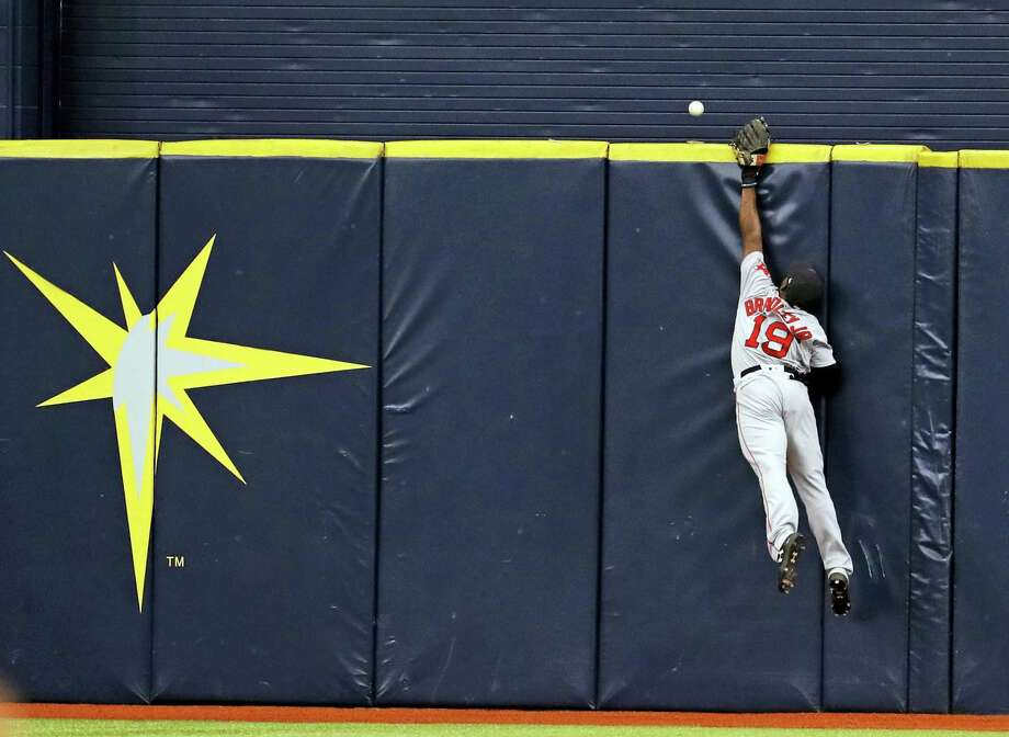 Red Sox center fielder Jackie Bradley Jr. reaches for a home run hit by Brad Miller in the eighth inning Sunday. Photo: Mike Carlson — The Associated Press  / FR155492 AP
