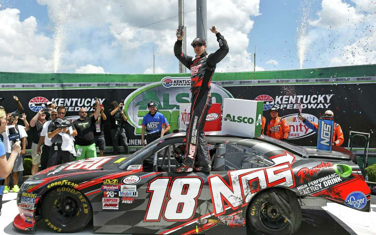 Xfinity Series driver Kyle Busch (18) celebrates in Victory Lane following his win in the Xfinity race at Kentucky Speedway on Saturday.