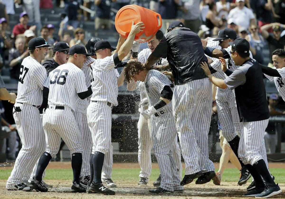 The Yankees' Brett Gardner (11) showers teammate Clint Frazier after Frazier's walk-off home run.