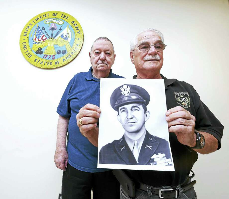 Frank Carrano (left) of East Haven and Daniel McHale of Avon are pictured with a photograph of Robert Nett from his days as a captain in the U.S. Army during World War II. Photo: File Photo